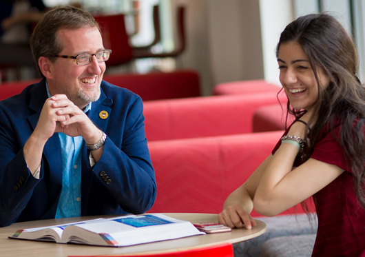 An academic advisor laughs with a student.