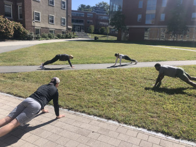Regis students doing pushups on the Quad at the Weston campus