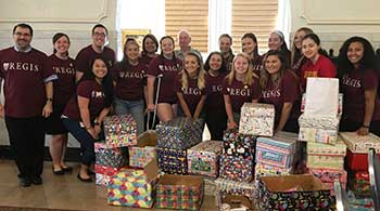 Members of the Regis community pose in front of a pile of boxed Birthday Wishes kits.