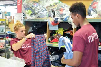 A pair of Regis students sorting clothes a Candles to Crayons