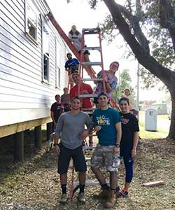 Regis students on a service trip to posing around a ladder while helping to renevate a house.