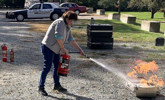 A photo of someone using a fire extinguisher to put out a stove fire