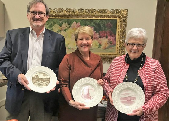 Patricia McNerney Kelleher, her son John and President Hays pose with donated Wedgewood dinner plates