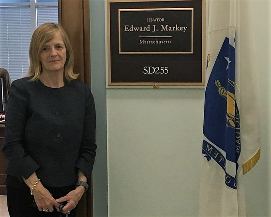 Dean Welsh poses beside the plaque for Senator Markey's office