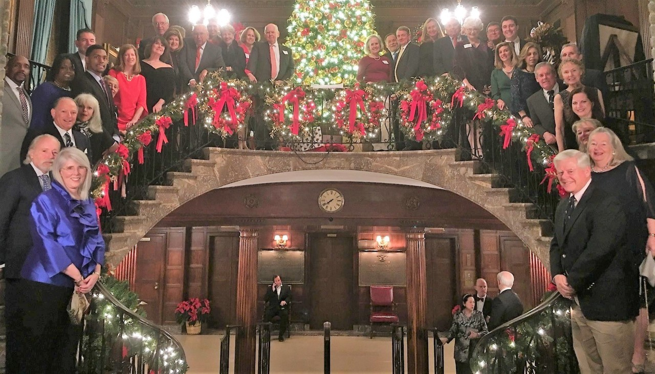 The Regis Board of Trustees and Administrative Council pose on stairs decorated for Christmas in New York City