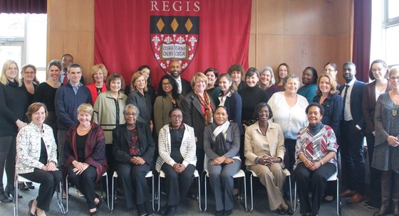 Attendees at the Coalition to Advance Patient Care in Haiti meeting pose in front of a Regis banner