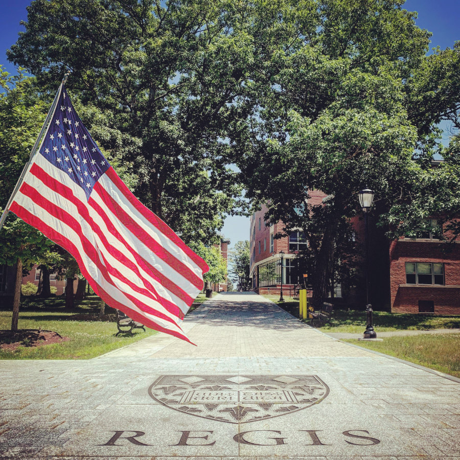 Photo of an american flag flying over the Great Walk on Regis' Weston campus