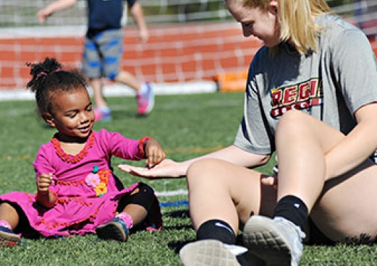 Children's Center student on an athletics field with a Regis College student
