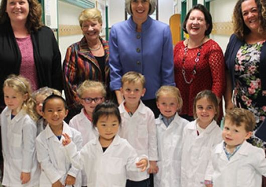 Regis Children Center staff with Congresswoman Clark behind a group of students in white lab coats