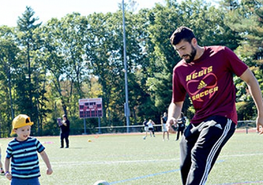 Regis College Children Center student playing soccer with a Regis College student