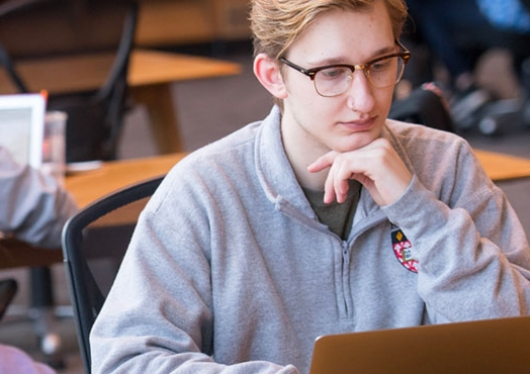 Regis College student in library