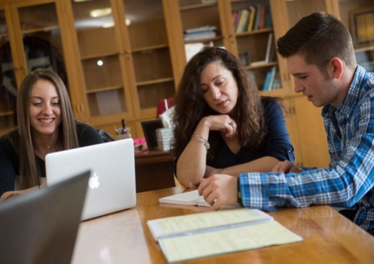 male and female students talking with librarian