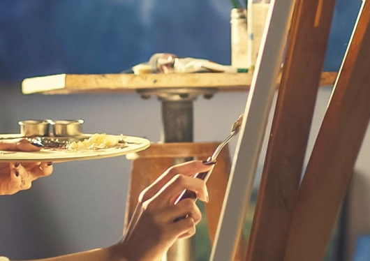 A student paints an image at an easel stand.
