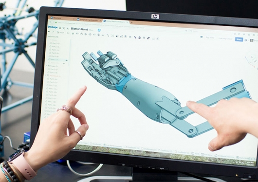 Close-up of a computer screen showing schematics of a prosthetic arm with two hands pointing at different points