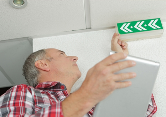 man checking fire alarm and lights