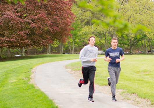Male students running on campus greens