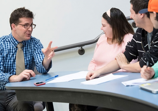 A professor speaks with students at a desk in a classroom