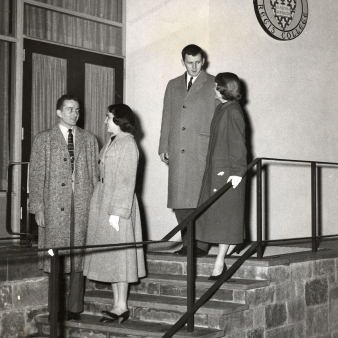 A black and white photo of two couples on the original front steps of Maria Hall