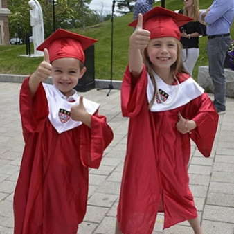 A photo of two Children's Center students in their graduation robes