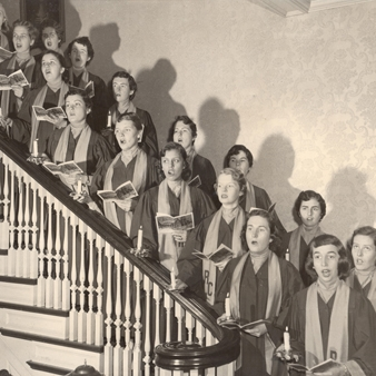 Archival photo of the Regis Glee Singers on the stairs in Morrison House