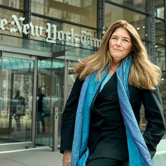 A photo of Carol Giacomo '70 standing in front of the New York Times building