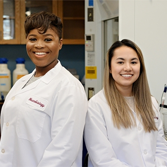 A photo of Andriana Harris '19 and Diana Tran, '16 in lab coats.