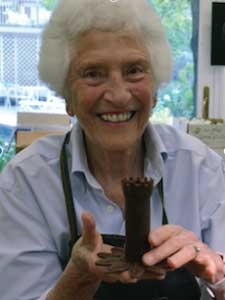 Nancy Schön holding a sculpture of Norman Tower in her workshop