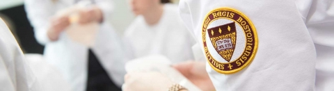 A close up photo of the shoulder of a Regis College nursing student with a Regis seal patch
