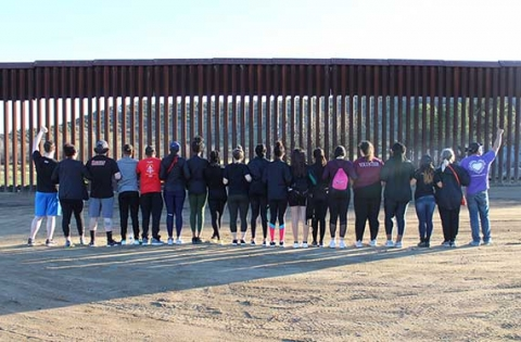 Regis students line up in front of the border wall in southern California during a service trip