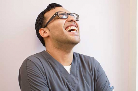 Male student in medical scrubs laughing
