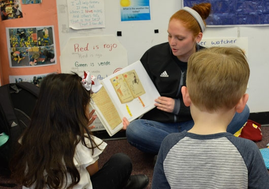 Student teacher reading to children