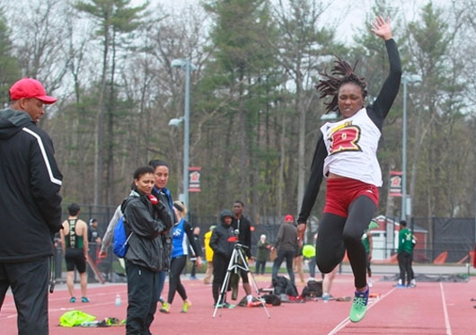 Regis women's long jumper in mid air
