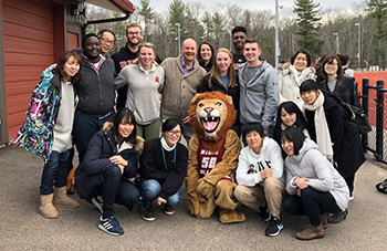 Students from Kyorin University pose with the Regis mascot outside of the playing fields